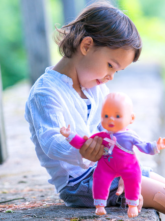 Cute little girl holding her doll Standard-Bild - 106318285