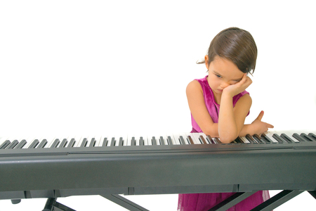 little girl being tired while practising the piano Standard-Bild - 106318288