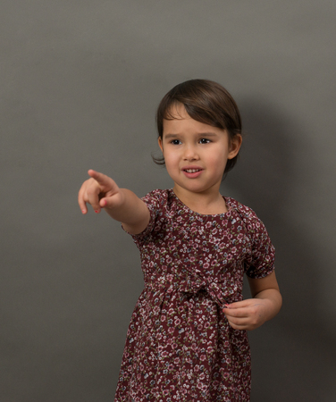 Young little girl pointing finger isolated