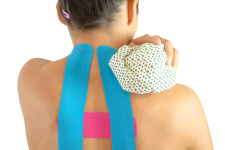 Woman with kinesiotapes applying ice bag on shoulder