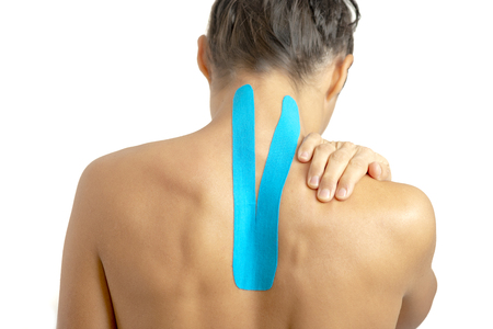 Female back with physio tape on white background