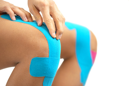 Woman applying blue kinesio tape on the injury knee