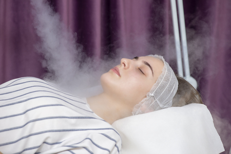 Beauty treatment of young female face, ozone facial steamer