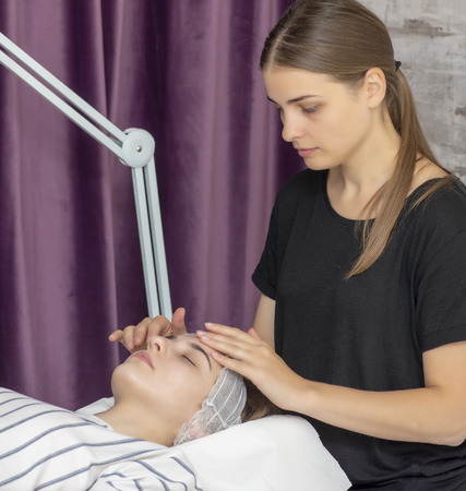 Relaxed young woman getting facial massage at spa salon Фото со стока