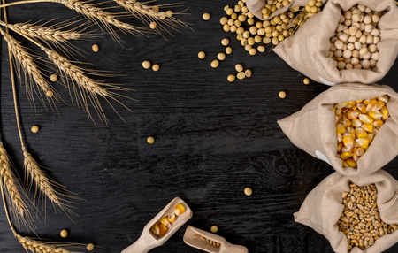 Small bags with various grains and cereals on wooden table, top view, copy space