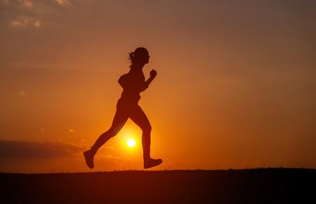 Silhouette of the running girl at sunrise.