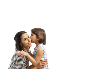 Portrait of happy daughter kissing her mother, isolated on white background