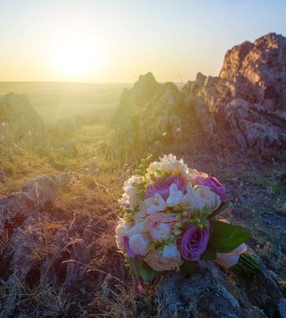 wedding bouqet near a hill at sunset