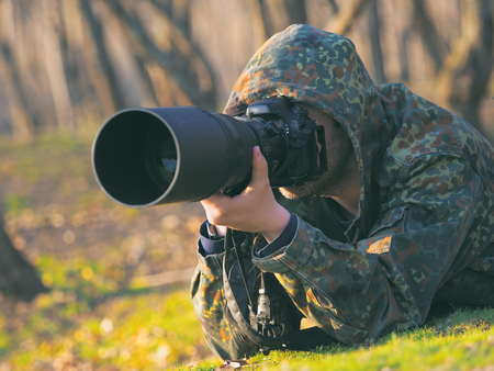 Wildlife, nature man photographer in camouflage outfit shooting, taking pictures Banco de Imagens