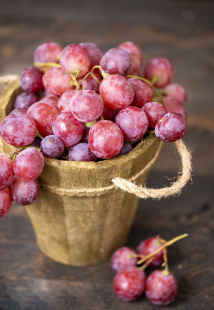 Rose grapes in wooden bucket on a woden table