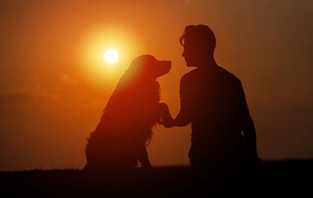Der junge Mann sitzt draußen, trainiert seinen Hund und schüttelt sich an einem Sommerabend die Hände, umrahmt vom Sonnenuntergang am Himmel Standard-Bild