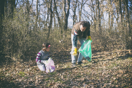 father and daughter gathering garbage in the park