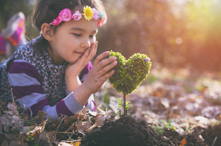 Beautiful little girl planting a heart-shaped tree and dreaming of a beautiful future