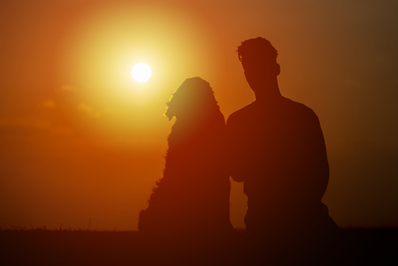 young man is sitting outside with his pet dog,  on a summer evening, silhouetted by the sunset in the sky Stock Photo