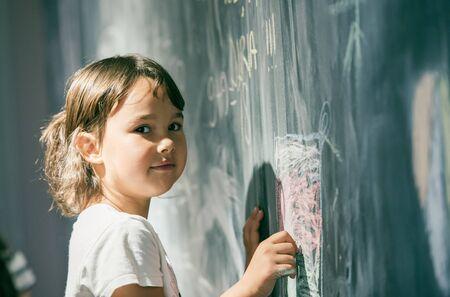 Schönes kleines Mädchen, das auf einer Tafel am Spielplatz zeichnet