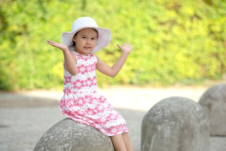 Adorable little girl wearing white hat sitting on stairs on warm and sunny summer day Stock fotó