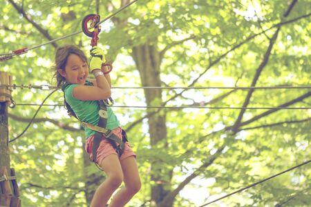 Happy little girl on zip line between trees