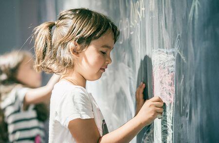 Beautiful little girl drawing on a blackboard at playground Stock fotó