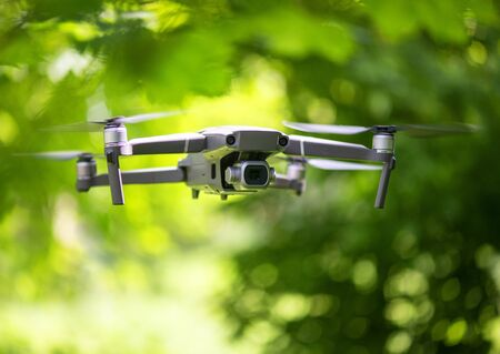 Flying drone with camera hovering inside a forrest, natural background