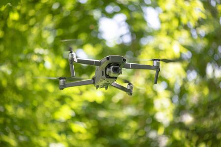 Flying drone with camera hovering inside a forrest, natural background Stock fotó - 129955831