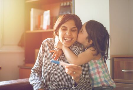 Mother enjoying with her daughter while looking at the positive pregnancy test