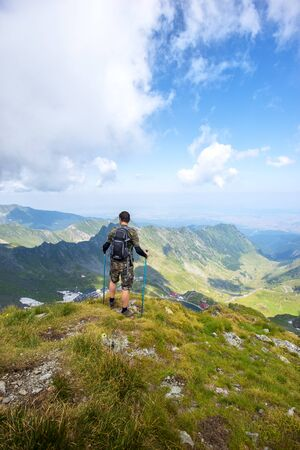 Successful active man hiker on top of mountain enjoying the view. Travel sport lifestyle concept