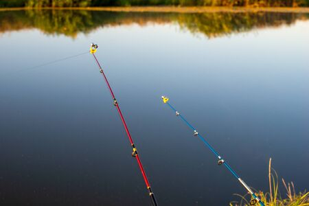 Fishing rod, spinning reel, on the background quiet pond. Banco de Imagens