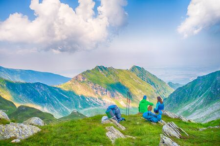 Back shot of young couple sitting down in the mountains on edge of cliff, admiring the view Stock fotó