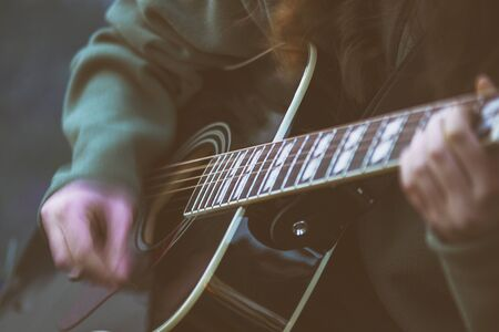 Close up womans hands playing acoustic guitar with the sensation of hand movement Stock fotó