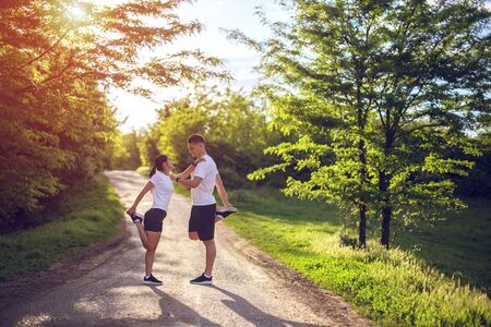 Young couple stretching legs on a road at the park Stock fotó