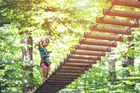 Little girl climbing in adventure park. Boy enjoys climbing in the ropes course adventure. Zdjęcie Seryjne