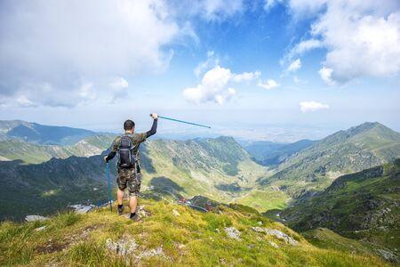 Erfolgreicher aktiver Wanderer auf dem Berg, der die Aussicht genießt. Reisesport-Lifestyle-Konzept