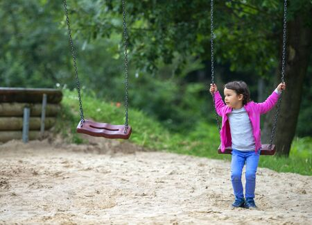 Cute little girl playing on swing in park