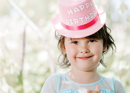 little girl with a happy birthday hat