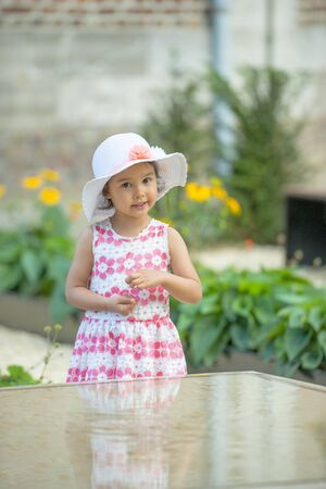 Adorable little girl wearing white hat on warm and sunny summer day