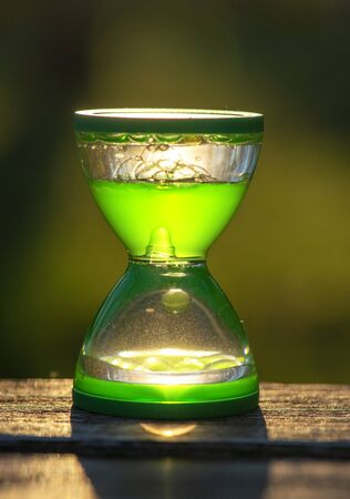 green  hourglass on wooden table in nature