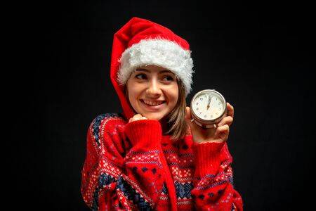 girl in Christmas dress with clock in her hand