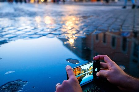 Man taking pictures of the cathedral of Saint Peter from the Vatican, reflected in the pond