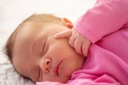 Cute little newborn sleeping with his finger on face