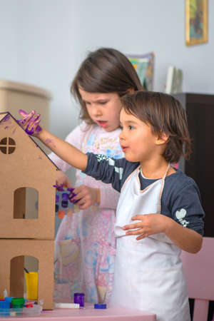 Two little girls playing with paint when crafting