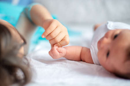 newborn baby with her older sister together on the bed holding each other`s hand
