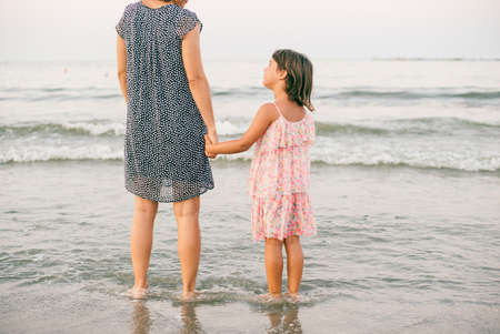 Mother and daughter enjoy together at sunet on the beach 版權商用圖片 - 155958040