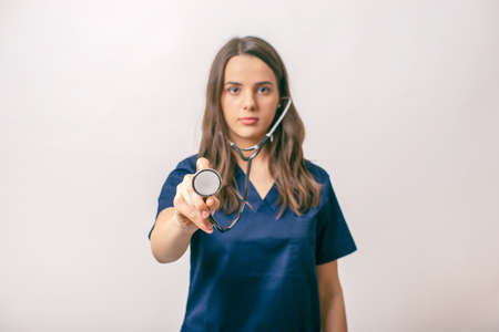 Beutifull young medic woman  holding a stethoscope, isolated over white
