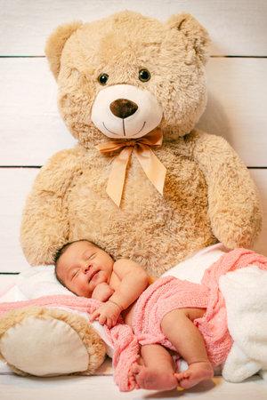newborn sleeping on a teddy bear in studio 免版税图像