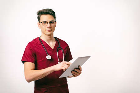healthcare and medicine concept - young male doctor with stethoscope and tablet in hands