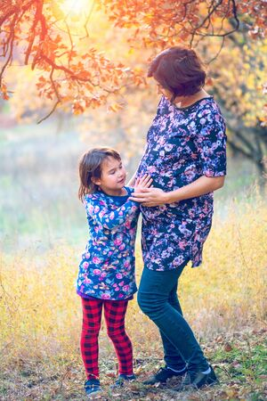 Happy family. Pregnant mom and little daughter hugging and kissing at sunset in autumn in forest. Laughter, happiness and fun together