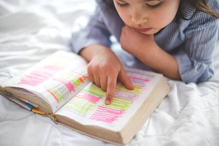 Little girl reading from Bible while lying in bed. Fetita citind din biblie in timp ce sta intinsa in pat. 版權商用圖片