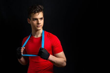 Young athlete in with red t-shirt stands with a blue sports elastic band around his neck after an workout.