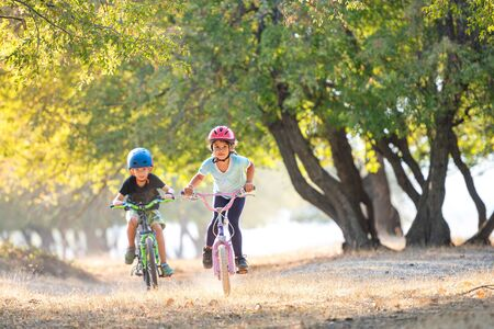 Happy girl and boy having fun in autumn park with a bicycle on beautiful fall day. Active kids wearing bike helmet