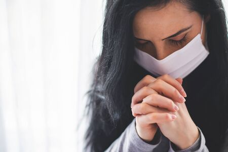 Portrait of woman with surgical mask praying
